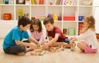 En gruppe børn leger med klodser på gulvet