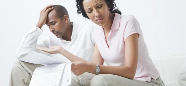 Kærestepar ser bekymrede ud over nogle regninger og dokumenter