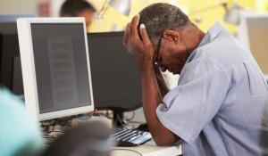 Mand tager sig til hovedet foran en computer